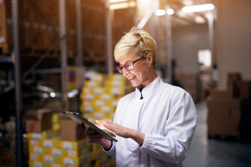 Woman in food warehouse with tablet